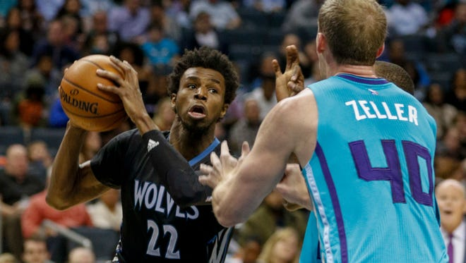 Minnesota Timberwolves forward Andrew Wiggins, left, looks to pass around Charlotte Hornets center Cody Zeller in the second half of an NBA basketball game in Charlotte, N.C., Saturday, Dec. 3, 2016. Minnesota won 125-120. (AP Photo/Nell Redmond)