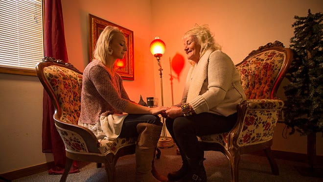 Medium Janine Ambrose, right, gives a reading of Kristi Beyer of Waterloo in her office Monday Oct. 12, 2015. Janine offers intuitive counseling, regression therapy and Reiki healing.
