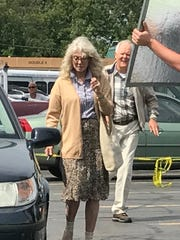 "Blythe Danner and John Lithgow act out a scene for ""The Tomorrow Man"" in the parking lot of the Gates Big M."