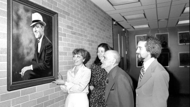 A group looks at a painting of Mayor John Gittone at Vineland City Hall in 1978.