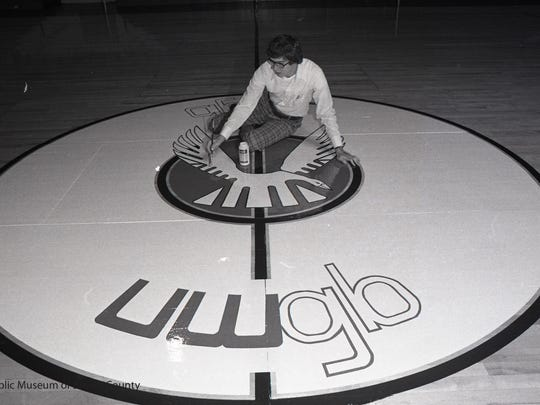 A student paints the Phoenix logo on the basketball court at the University of Wisconsin -  Green Bay in 1975.