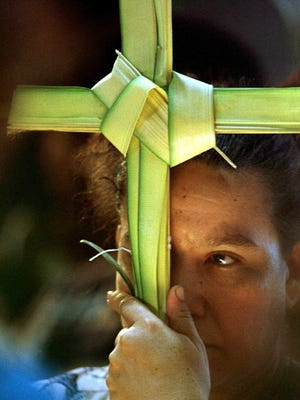 -  -A Nicaraguan woman holds a palm frond in the shape of a cross at the Palm Sunday service at the national cathedral in Managua, Nicaragua on Sunday, March 28, 1999. Palm Sunday marks Jesus Christ's entance into Jerusalem, before his crucifixion, as palm branches were laid in his path. The palm fronds are sold for 11 U.S cents per frond at the entance of the cathedral. The fronds are usually taken home after services and kept in a safe place, where they are believed to scare off the spirit of the devil (AP Photo/Anita Baca)