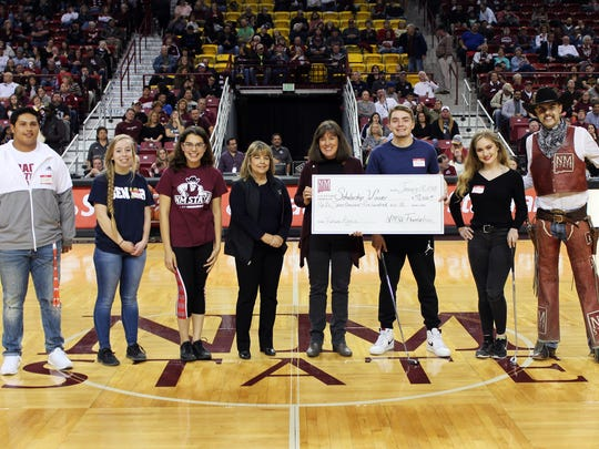 The NMSU Foundation sponsored a scholarship-earning, putt-putt competition during an Aggie Men's basketball game last Thursday for incoming freshmen. Pictured, from left, are Justin Lopez, Brianna Douds, Allison Hendricks, NMSU Foundation chief operating officer Tina Byford, associate vice president of alumni relations Leslie Cervantes, the scholarship recipient Aaron Ramsey, Andrea Campos and Pistol Pete.