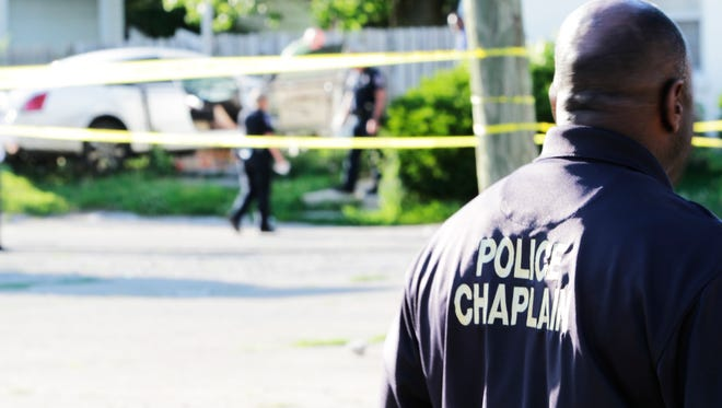 Police chaplain David Coatie stands arrives at the scene as detectives investigate an fatal officer-involved shooting on the city's Northeastside Tuesday evening.