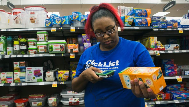 Natashia Ingram, a ClickList dedicated associate at a Kroger store in East Memphis, scans a grocery item as she shops for a customer Thursday, Feb. 16, 2017.