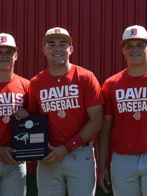 Trey Parker, Cole Martin, and Dane Parker smile together while holding the 2019 District Champion plaque.