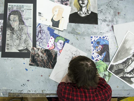 Chris Jones uses a black ink pen on one of his art