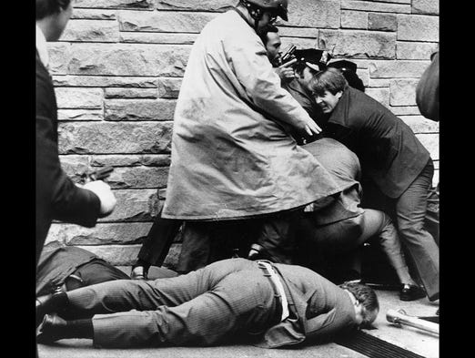 White House press secretary James Brady lies wounded on the sidewalk outside a Washington hotel after being shot during an assassination attempt on U.S. President Ronald Reagan, March 30, 1981.  In the background secret service agents and police wrestle the alleged assailant to the ground.