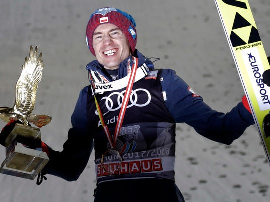 FILE - In this Jan. 6, 2018, file photo, Poland's overall winner Kamil Stoch lifts the trophy after the winning ceremony for the Four Hills Ski Jumping event at the ski jump in Bischofshofen, Austria. With an historic win on the World Cup circuit, double Olympic champion Kamil Stoch is in peak form as he aims to defend his ski jumping titles at the Pyeongchang Games. (AP Photo/Matthias Schrader, File)