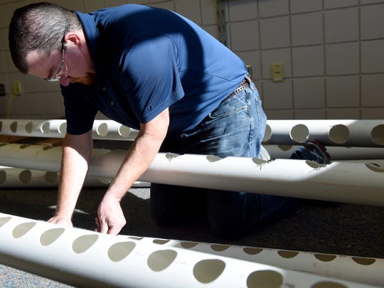 Kyle Brunick builds a hydroponics system in Linda Pinz-Valdez's classroom at Oscar Howe Elementary on Tuesday. Pinz-Valdez won a $5,000 grant to create a hydroponics system and grow plants during the school year.