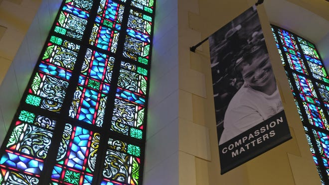 In this Tuesday, Feb. 12, 2019 photo, a banner hangs by a stained glass window in the sanctuary at Glide Memorial United Methodist Church in San Francisco. The United Methodist Church officially opens its top legislative assembly Sunday, Feb. 24, 2019, for a high-stakes three-day meeting likely to determine whether America's second-largest Protestant denomination will fracture due to long-simmering divisions over same-sex marriage and the ordination of LGBT clergy.