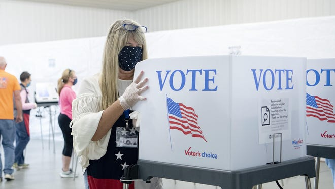 Poll worker Lois Walker cleans a voting computer and privacy shield after a voter cast a ballot during the first day of early voting at the Henderson County Board of Elections Office in Hendersonville Thursday. Each voting table was disinfected between each voter.