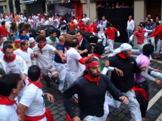 Matt Stock (center foreground) was one of the runners trying to avoid the bulls during the 2014 Running of the Bulls in Pamplona, Spain.