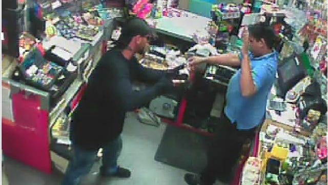 A still image from video surveillance cameras during an armed robbery at a Mobil gas station in Fort Myers.