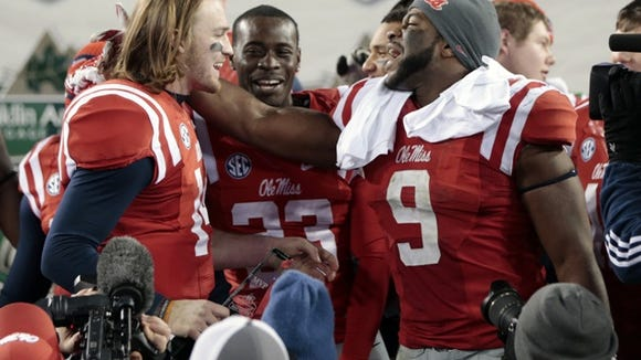 Mississippi quarterback Bo Wallace, left, celebrates with linebacker D.T. Shackelford (9) after beating Georgia Tech in the Music City Bowl on Monday, Dec. 30, 2013, in Nashville, Tenn. Mississippi won 25-17. (AP Photo/Mark Humphrey)