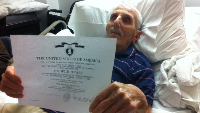 John LaPuzz, 96, holds his Purple Heart medal citation at the Veterans Memorial Home in Paramus, N.J., where he lives.