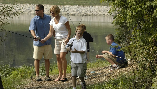 The Wentzel family of Mason enjoys spending family time fishing at the Pine Hill Lake in Mason. Brent and Kim work on a line while Austin, 8, (in white) gets ready to cast. In the background at right is Andy, 9 and Aaron, 6 (back to the camera).  Photo by Jim Callaway.