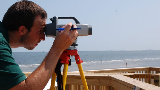 Chris Nealan, a U.S. Geological Survey technician, records the elevation of a pre-installed bracket at the Childrens Beach House in Lewes. As storms approach, scientists will install tide sensors at these pre-set locations.