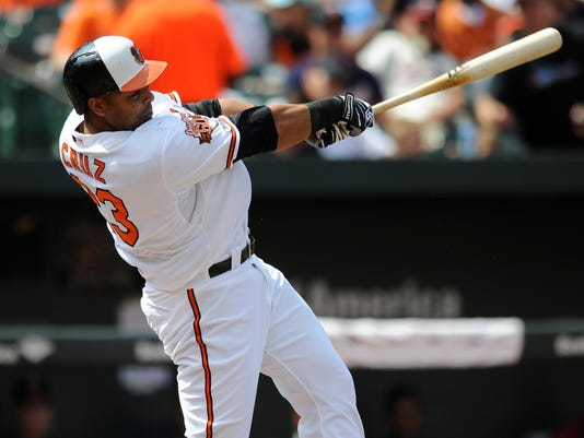 Baltimore Orioles' Nelson Cruz follows through on a solo home run against the Minnesota Twins in the third inning of a baseball game, Sunday, Aug. 31, 2014, in Baltimore. (AP Photo/Gail Burton)