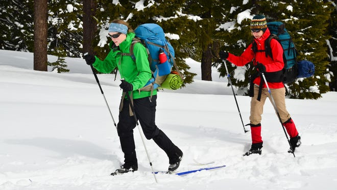 """""""Two women cross country skiing with in the backcountry. Crater Lake National Park, Oregon."""""""