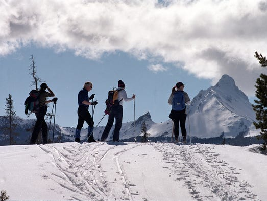 A group of skiers stands in front of a mountain skyline