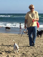 """Columnist, Bruce Fessier, is seen walking his dog at Huntington Beach during his """"staycation."""""""