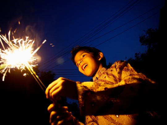 Boy playing with a sparkler; sparklers are illegal to use in Monterey County.