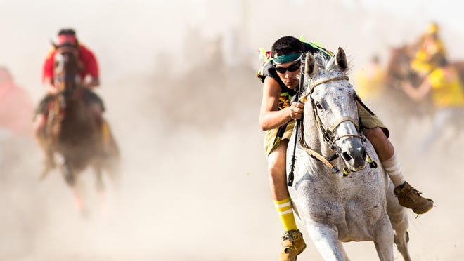 A rider from team Whitecap rides his horse at full gallup after a successful switch during the indian relays at the North American Indian Days in Browning on July 11. The relays, which entail a rider bareback racing two laps and switching horses halfway through each, were won by team whitecap.
