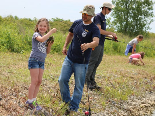 Wren Lewis, 7, poses after catching a fish during the refuge ranger camp at the Ottawa National Wildlife Refuge.