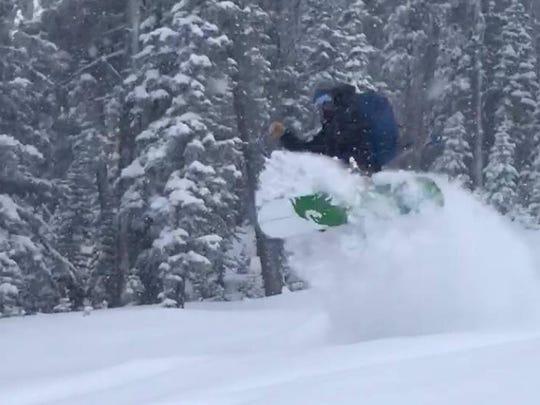 A snowboarder enjoys fresh powder that fell Sunday