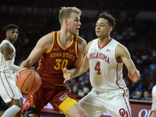 Iowa State's Hans Brase drives to the basket in front of Oklahoma's Jamuni McNeace during their game Friday, March 2, 2018, in Norman, Oklahoma.