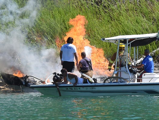 Emergency personnel work to extinguish a boat fire Tuesday near Lakeview Cove Marina on Bull Shoals Lake. A Piggott couple escaped the inferno by jumping from the boat.