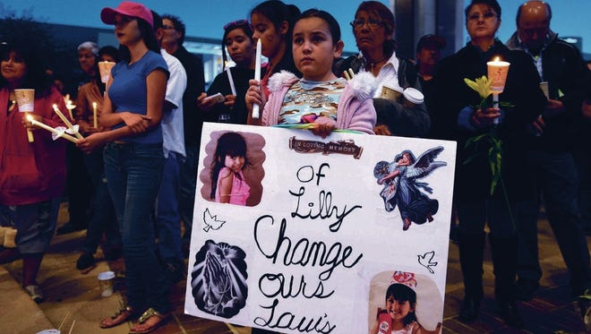 During a vigil on Civic Center Plaza in Albuquerque, 8-year-old Elizabeth Madrid of Albuquerque holds a poster to honor 4-year-old Lilly Garcia, who was shot and killed during an alleged road-rage incident.