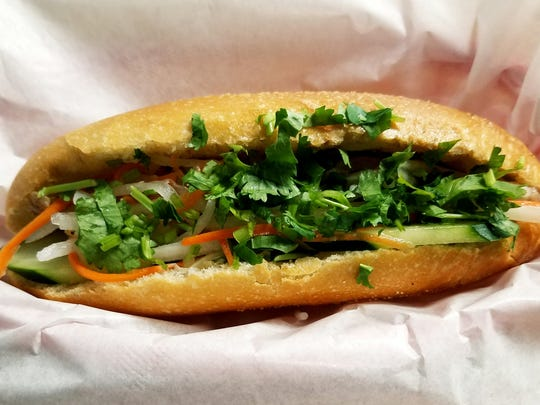 PHO 772's Vietnamese sub is made with your choice of chicken or pork. Pictured is one with pork, pickled carrots, cilantro, and cucumber on a crispy French roll.