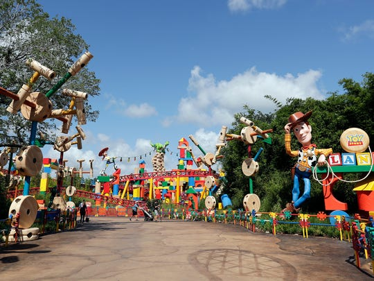 In this Saturday, June 23, 2018 photo, a statue of the character Sheriff Woody, right, greets visitors at the entrance Toy Story Land in Disney's Hollywood Studios at Walt Disney World in Lake Buena Vista, Fla.