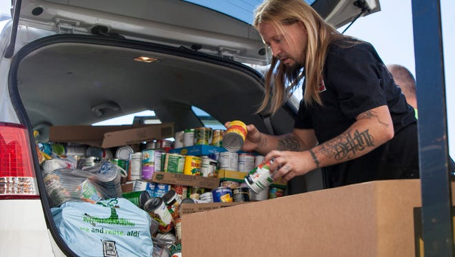 Micheal Keihn helps unload nearly 1200 lbs. of food being donated to the Second Harvest Food Bank of East Central Indiana Monday afternoon. Second Harvest was one of several charities funded by the Organ Trail Halloween house.