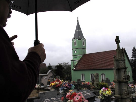 Government worker Ademir Rost points out a Lutheran church inside a cemetery where German-Brazilians are buried, during a tour of German-Brazilian areas of interest in the southern province of Rio do Grande do Sul, Brazil, Friday, June 28, 2014. German-Brazilians in the region are supporting Germany and Brazil at the World Cup soccer tournament, but if and when the two sides meet, they say they'll support Brazil. (AP Photo/Chris Brummitt)