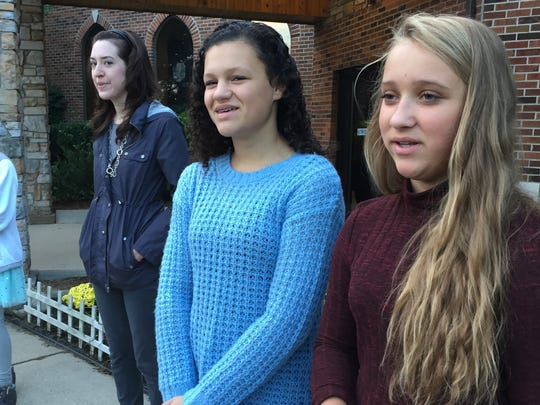 Students Lainey Spadafore, left, and Nicole Will lead a See You at the Flagpole event at Trinity Lutheran School.