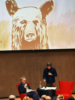 """Artist Dave Eggers, right, creates a painting while participating in a discussion about his exhibition """"Insufferable Throne of God"""" at the Nevada Museum of Art in Reno on April 2, 2015. Nion McEvoy, chairman and CEO of Chronicle Books, is seen on the left."""