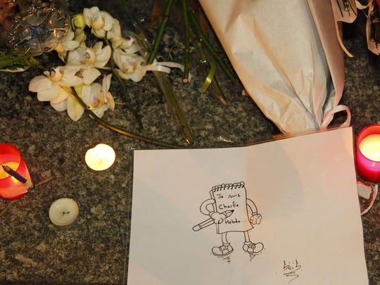 "Flowers, candles and a dawing reading ""I am Charlie Hebdo""  are placed on the pavement near the offices of French satirical weekly Charlie Hebdo in Paris after armed gunmen stormed the offices, leaving 12 dead."