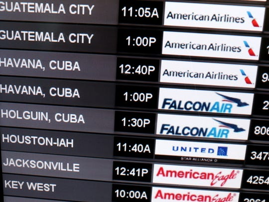 A sign shows the departure times for flights to Cuba