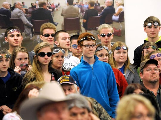 Dozens of area swimmers wearing swim goggles and caps silently protested the announced closure of the Zeugner Center pool on Tuesday in the board room of the Buncombe County Board of Commissioners meeting.