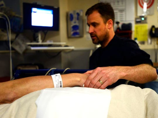 Registered Nurse David Schneider comforts a patients while discussing medication in the Mission Memorial Campus Emergency Department.