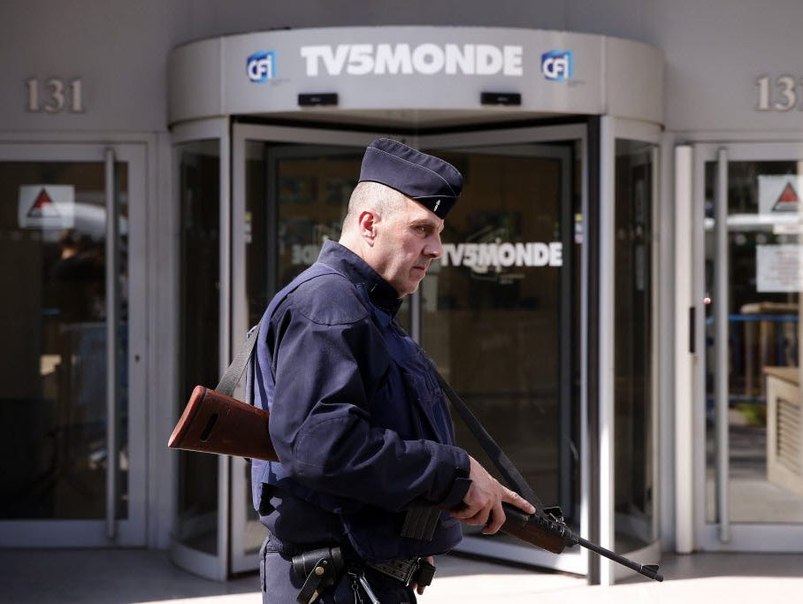 A French security guard stands watch at the entrance to a TV station that recently was compromised by hackers who temporarily left the station unable to broadcast.
