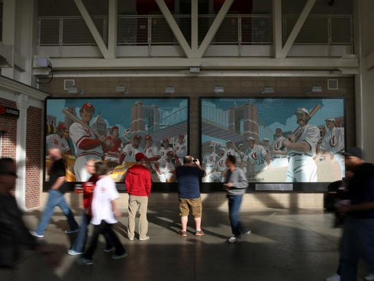 """Fans walk pass the """"Great Eight"""" mosaic mural at the main entrance of Great American Ball Park."""
