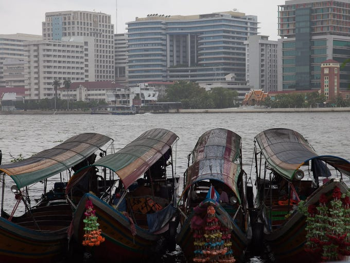 Old-fashioned boats float in front of modern buildings