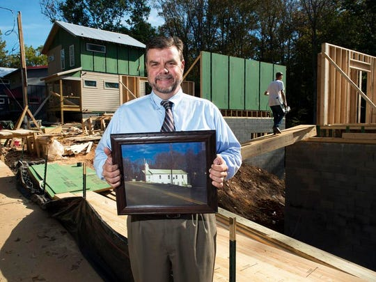 Pastor Ricky McCarson holds a picture near the site where his church, Sand Hill Baptist Church, once stood at 232 Sand Hill Road. The property is now being converted into town homes.