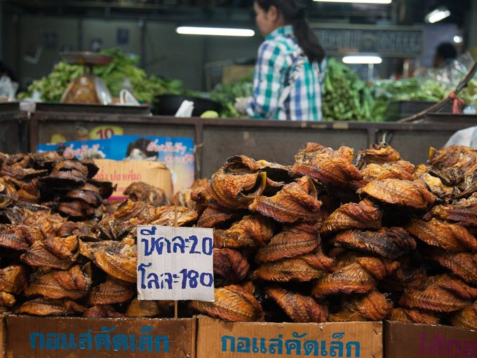Piles of fried fish await sale at a Chiang Mai market