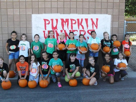 Students hold their winning pumpkins after racing in