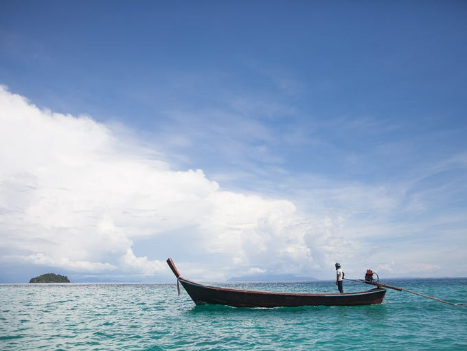 A driver steers his longboat in the Andaman Sea off